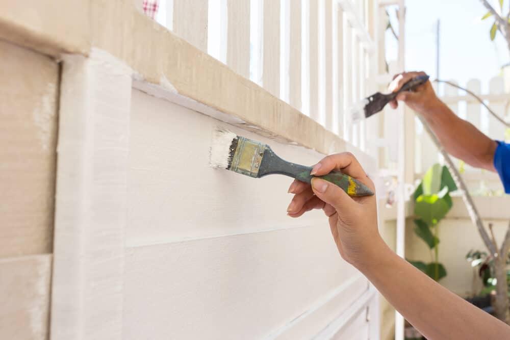Hand worker holding brush painting white on wood - Big Easy Fences