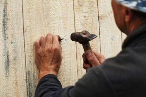 Man nailing a fence - Big Easy Fences